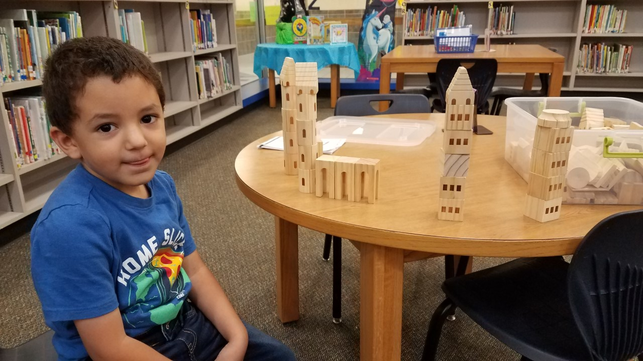 pre k student building a castle in the library